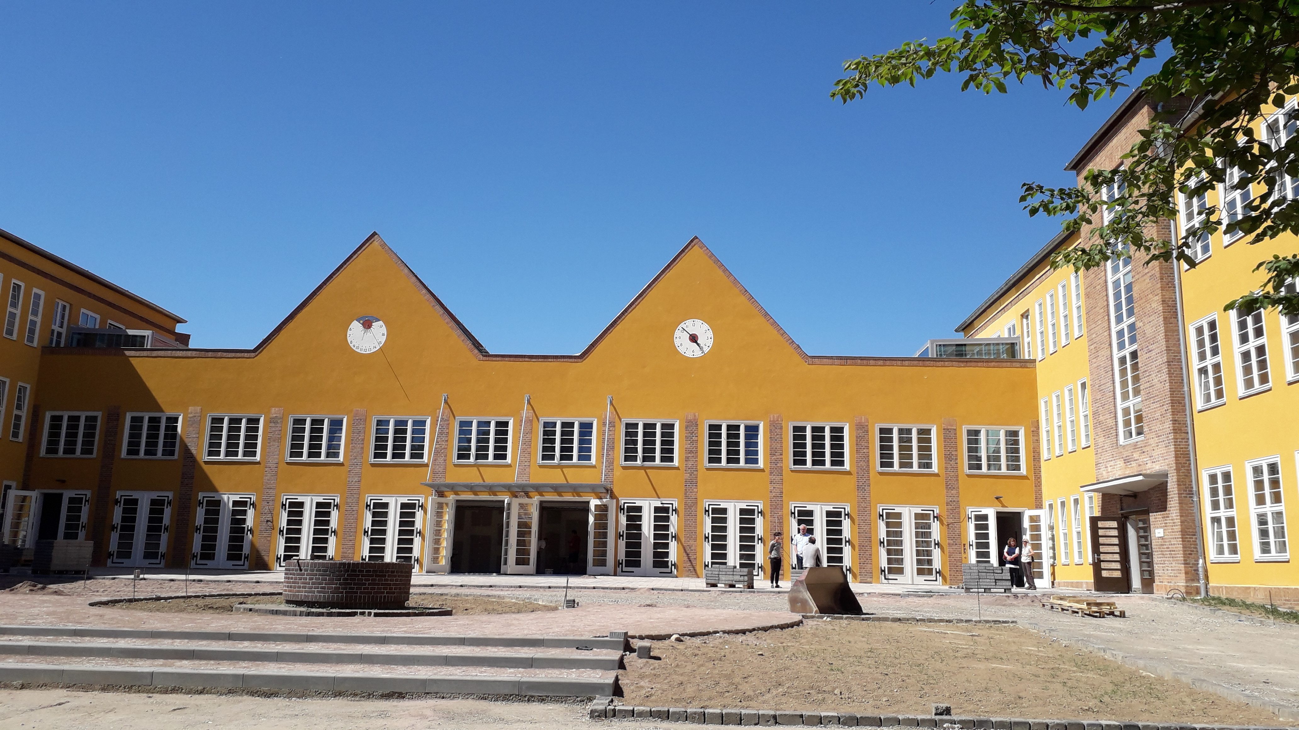 Der Empfangsbereich vor den Schultüren ist in seiner Form schon zu erkennen. Bäumerahmen die Schule ein und geben Schatten.